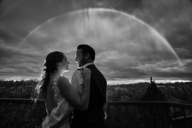 The couple pause for a wedding photography portrait under a rainbow at Eagle Crest Resort. Pete Erickson Photography.