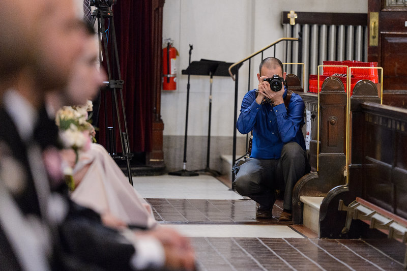Russ Hickman working in a church and photographing a ceremony.
