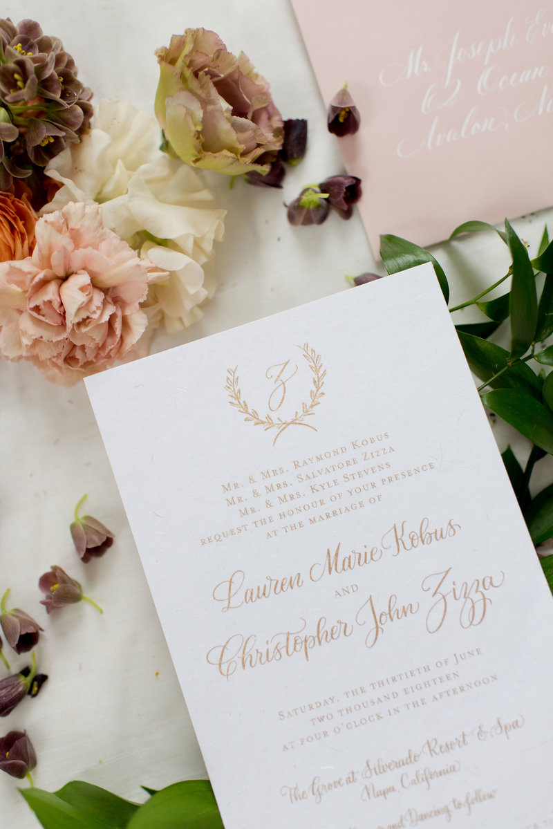 Closeup of wedding invitation on gold ink with custom calligraphy