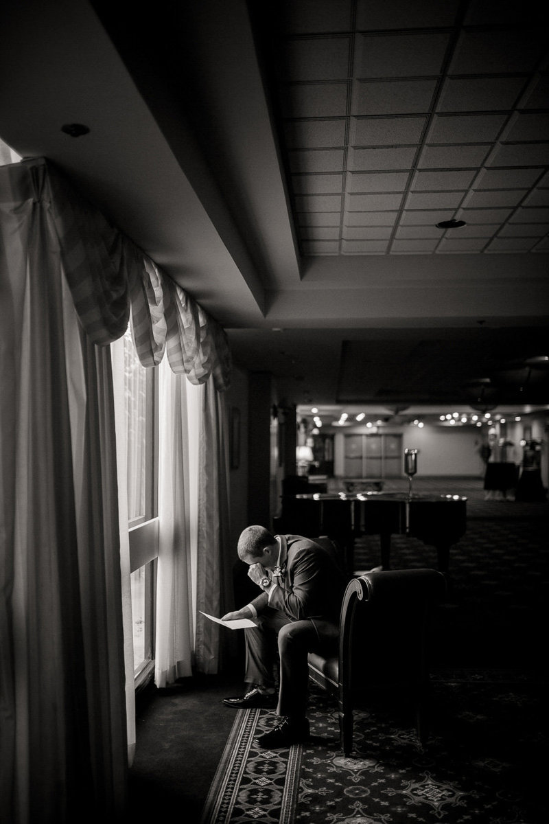 Groom reading his letter from his bride in window light at Marriott in downtown Knoxville by Knoxville Wedding Photographer, Amanda May Photos.