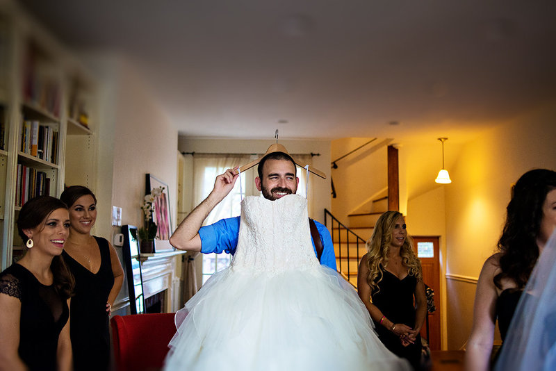 A silly shot of russ hickman holding the brides wedding dress.