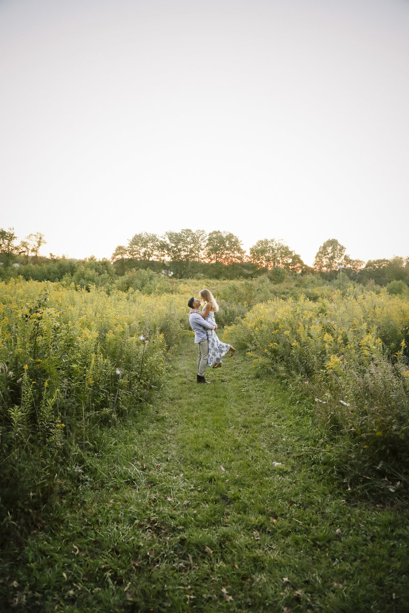 man holding woman in large lush field