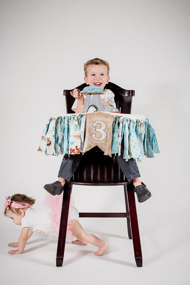 Little boy in a high chair turning two with his sister crawling under him in the studio with a white back drop by Knoxville Wedding Photographer, Amanda May Photos.