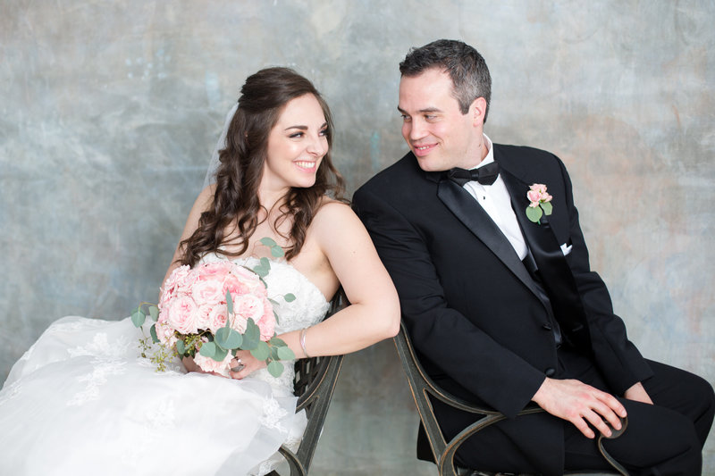 Roswell wedding couple lean back to back and smile at each other