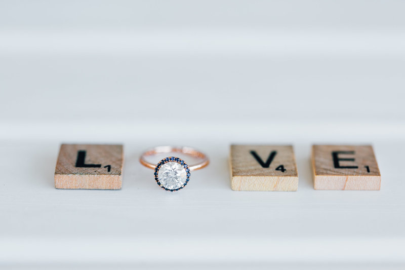 love spelled with scrabble letters and engagement ring