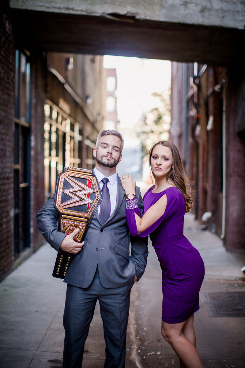 He holds WWE belt while she leans on his shoulder in an alley in downtown Knoxville by Knoxville Wedding Photographer, Amanda May Photos.