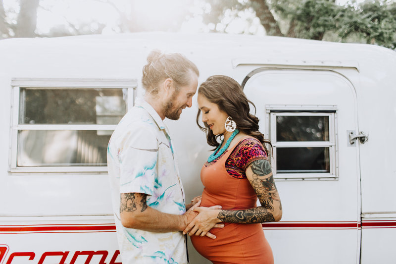 couple standing by scamp trailer pregnancy