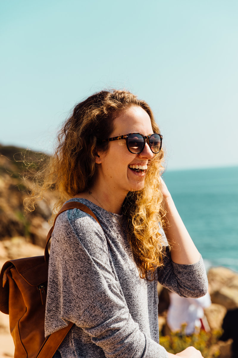 Woman laughing with wind blown hair during trip to Malibu, California