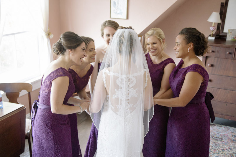 bride and bridesmaids laughing together on wedding day