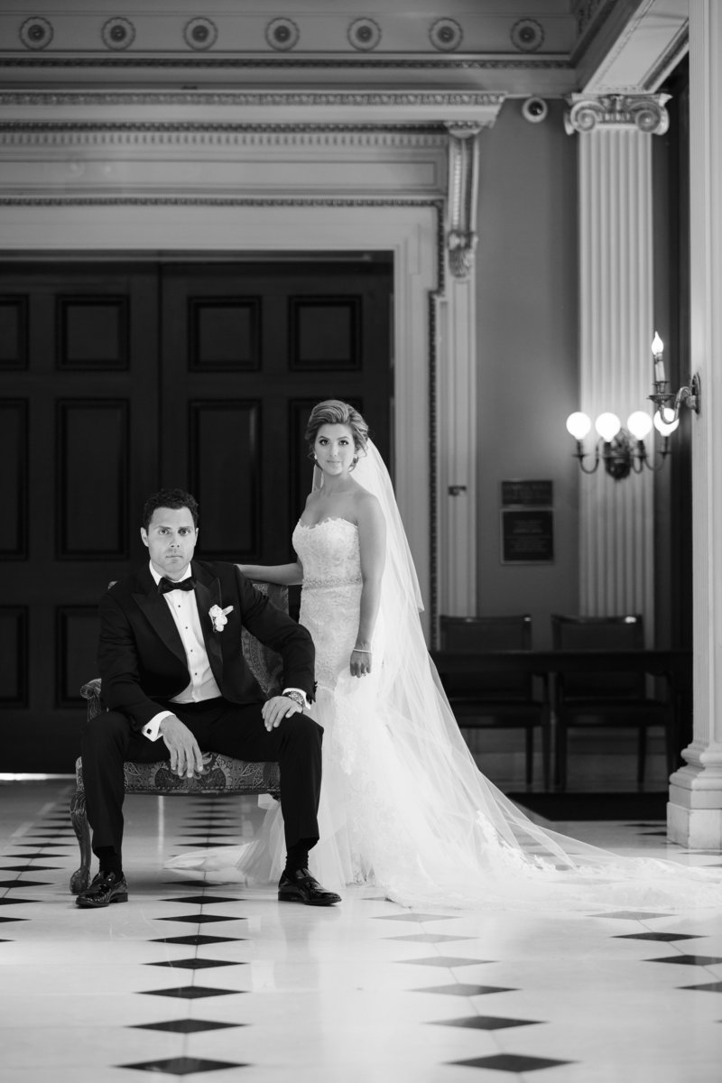 black and white dramatic portrait groom sitting and bride stands next to him
