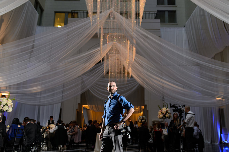 A wedding photographer working at a reception at the curtis center in philadelphia.