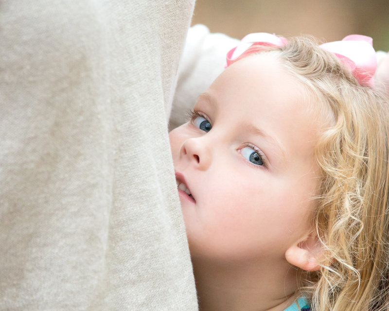 A girl peeks from behind her mother during a family photo shoot