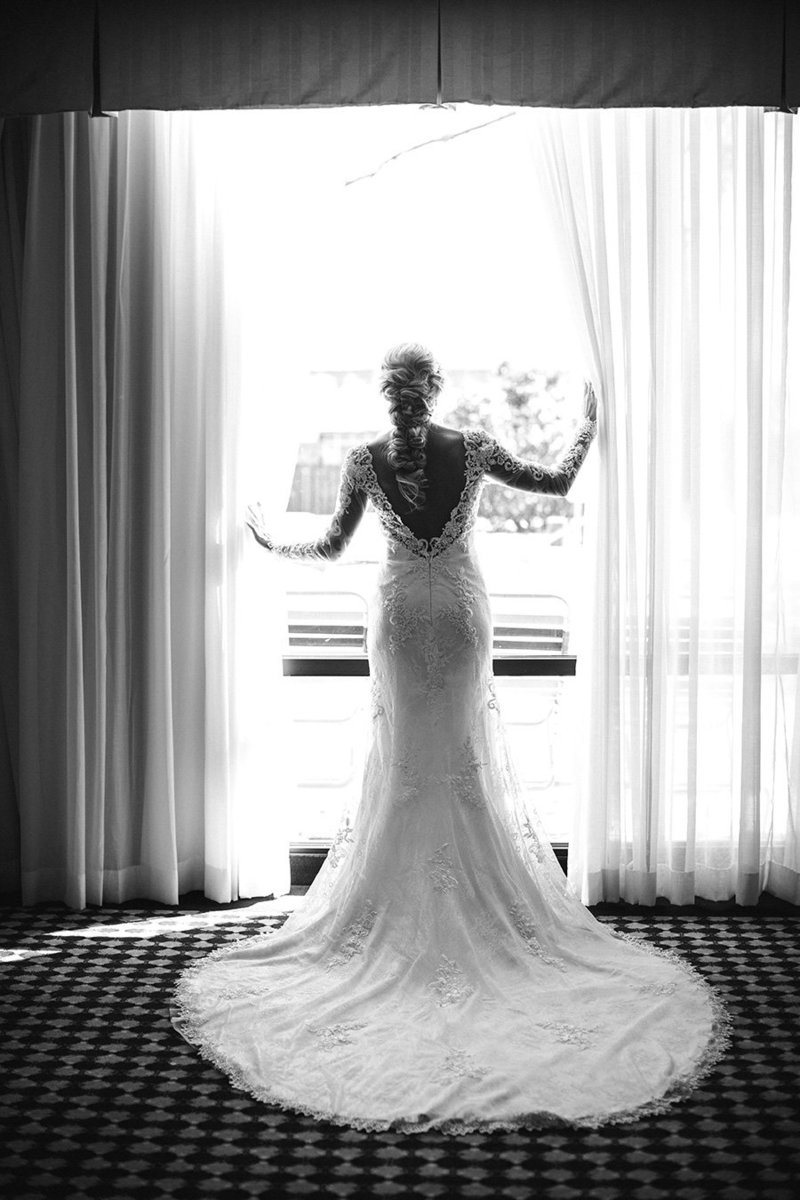 Black and white image of bride looking out window at Historic Westwood Wedding Venue by Knoxville Wedding Photographer, Amanda May Photos.