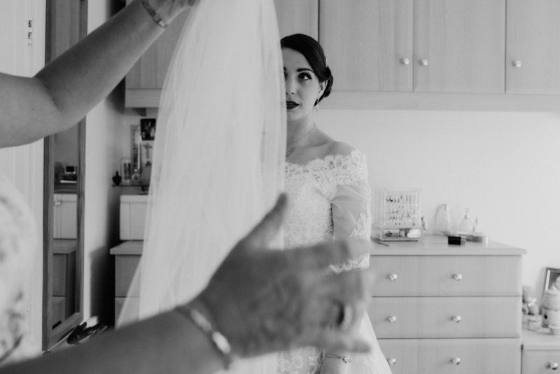 Bride about to put on veil.