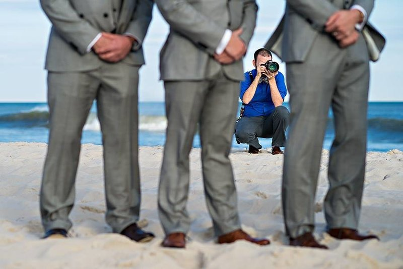 A creative image of Russ Hickman photographing a wedding on the beach in LBI, NJ.