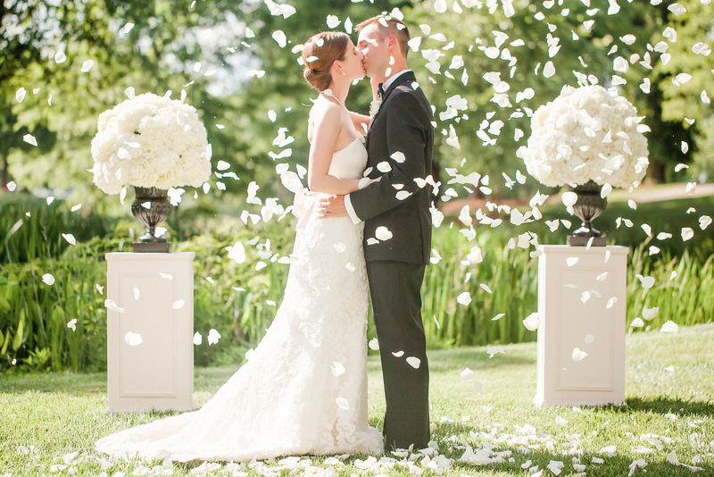 Bride and groom share a kiss whilst confetti petals are thrown, by Charlotte wedding photographer