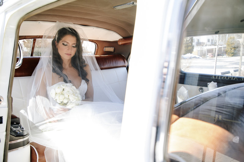 bride sits in rolls-royce car looking at bouquet