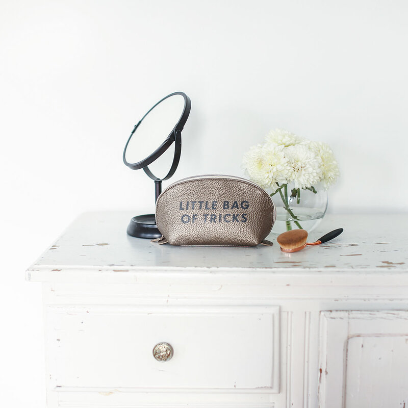 makeup bag on a bureau with a mirror and makeup brush