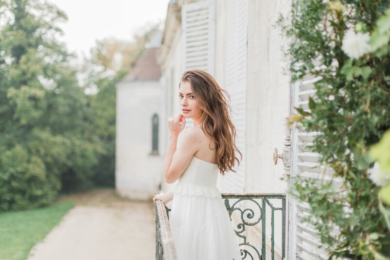 bride standing on balcony in champagne france on wedding day by costola photography