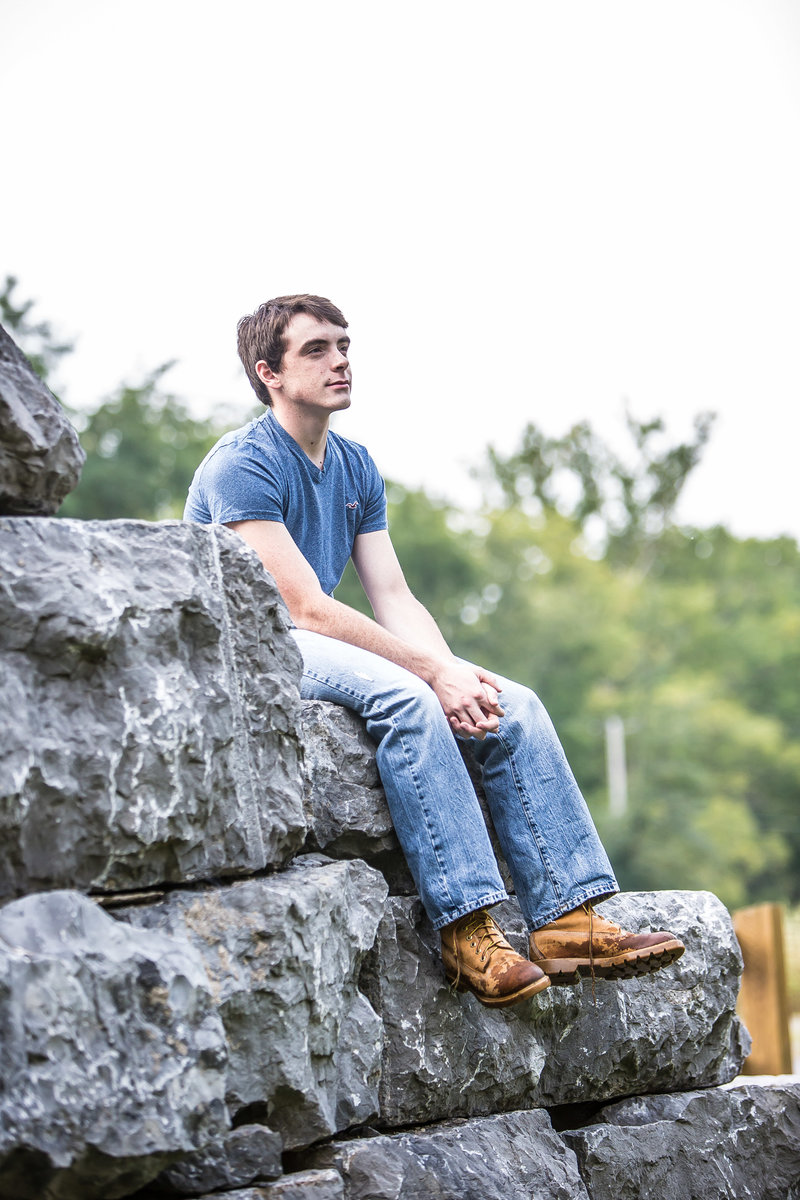Male Senior photo on large stone wall-73