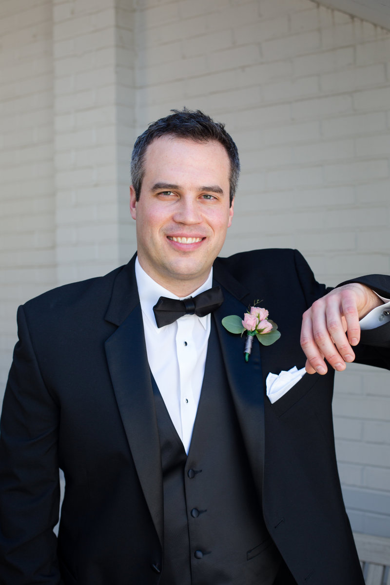 Groom in black tuxedo stands with arm bent with pink peony boutonniere