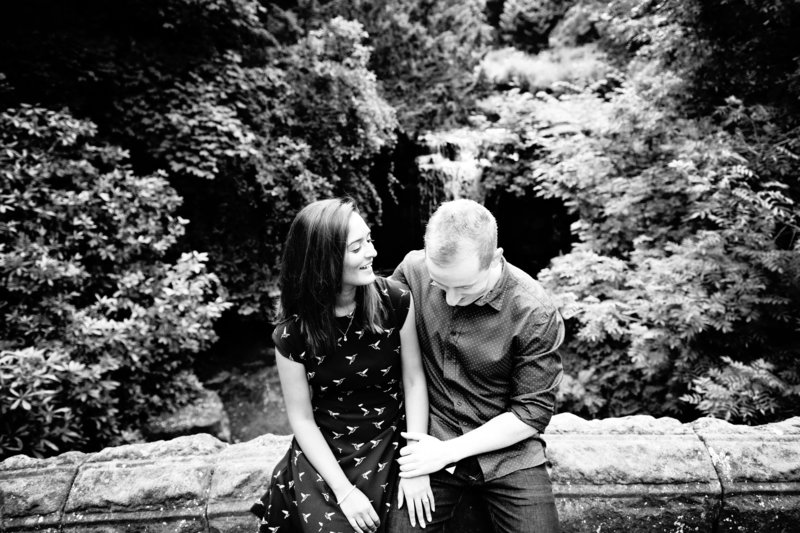 Couple relax and laugh on engagement session in a park in Newcastle