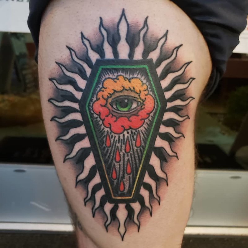 A color tattoo of a coffin with a crying eye inside.