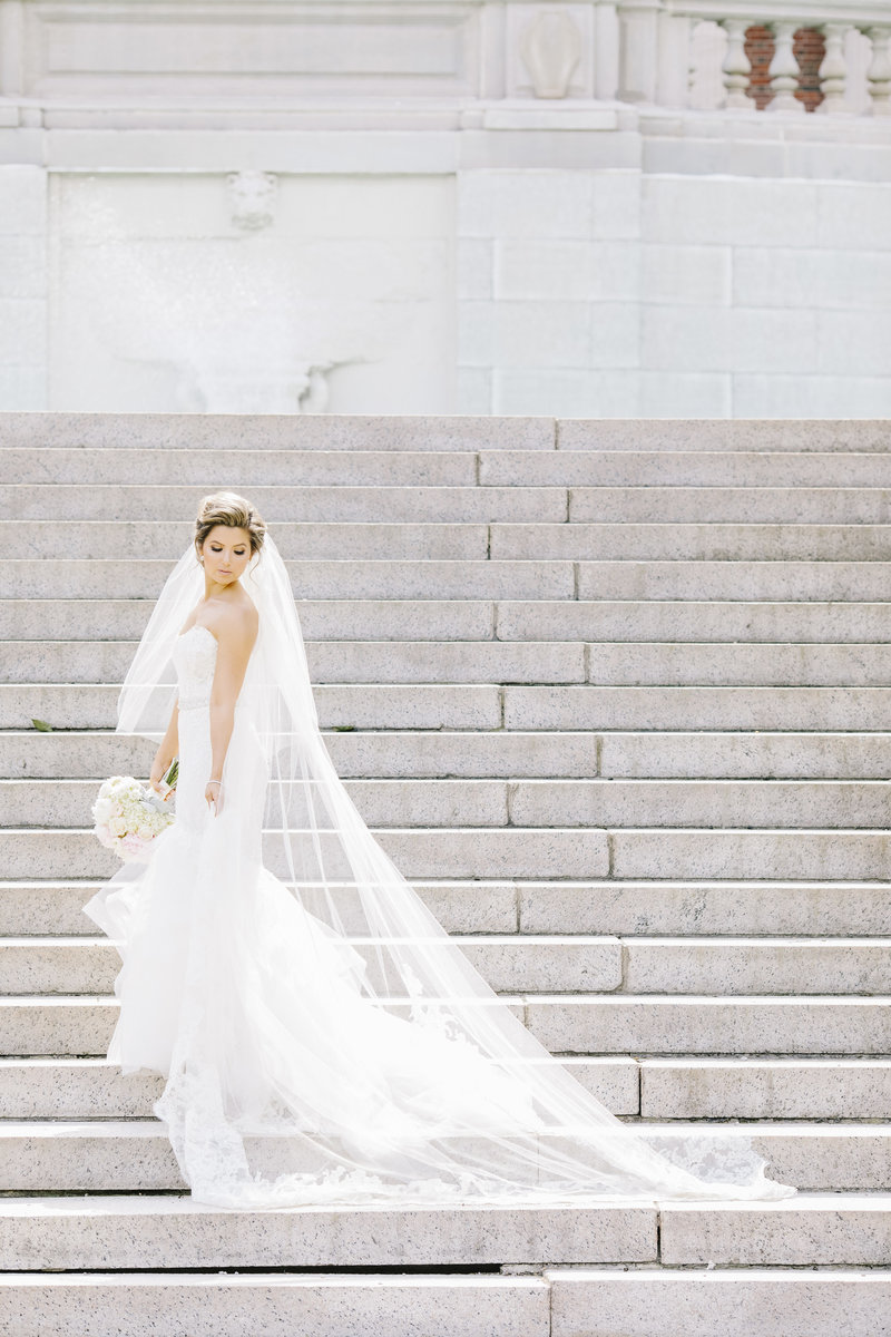 bride in amsale dress walks up grand staircase outside