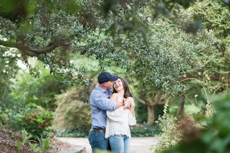 a guy wearing a blue button up shirt holding his fiance from behind with them looking at each other laughing at JC Raulston Arboretum
