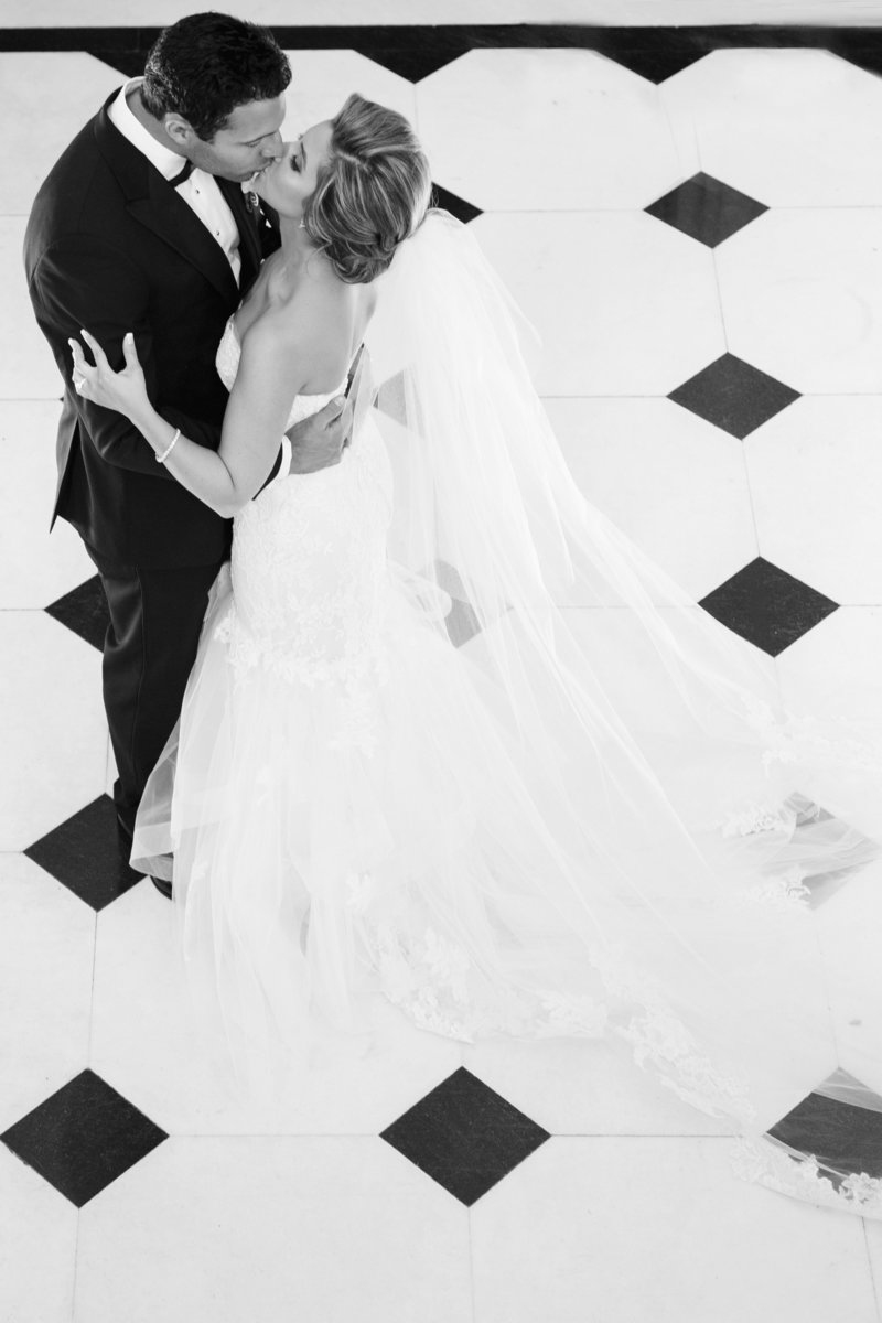 black and white bride and groom kiss standing on checkered floor