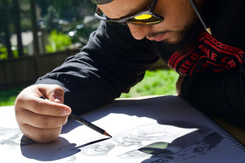 A man wearing sunglasses drawing a face with pencil.