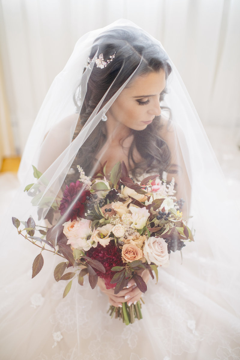 portrait of bride and her bouquet under veil