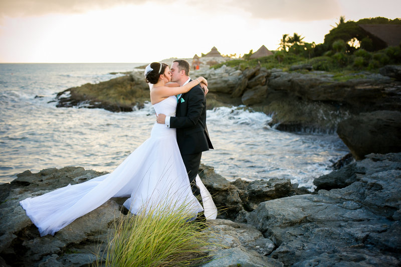 Bride and groom kissing on rocky beach in Mexico