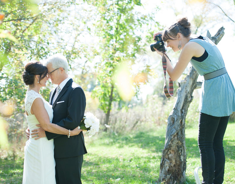 Behind the scenes at a real wedding in fargo featuring Kris Kandel photographing the bridal couple