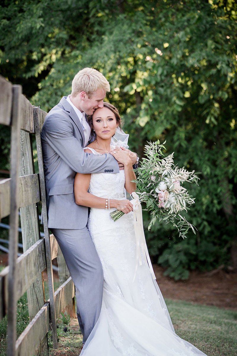 Groom's arms around bride's shoulders leaning against a fence at Hunter Valley Farm by Knoxville Wedding Photographer, Amanda May Photos.