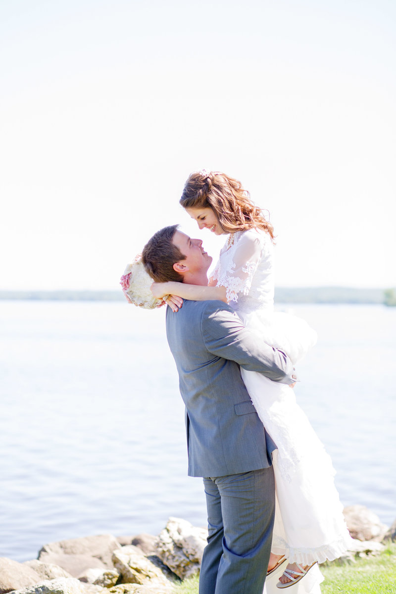 bride and groom embracing in front of a lake