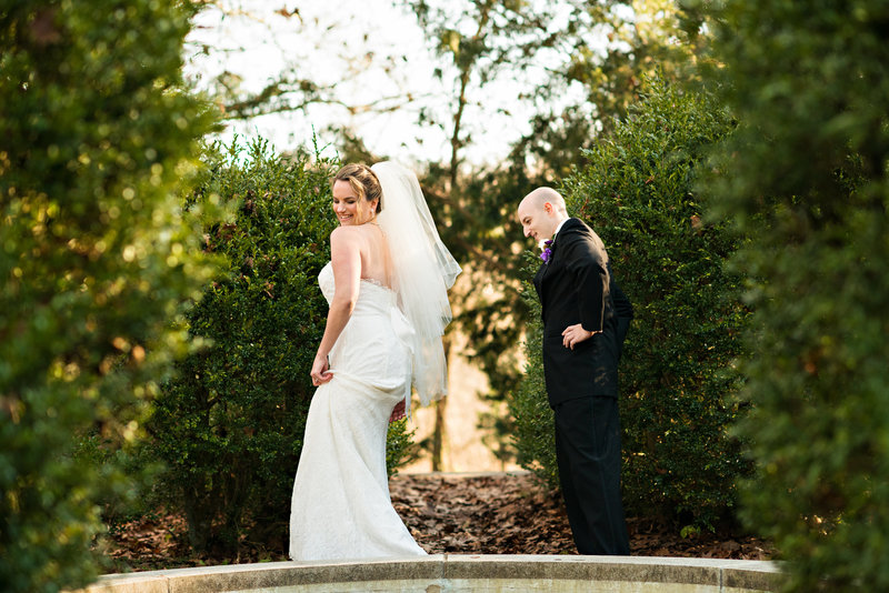 A groom checks out his bride during their first look at a wedding at ridley creek mansion.