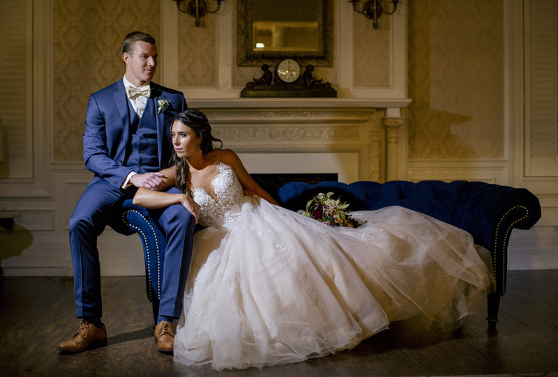 brides lays on couch groom sits on side  in large room