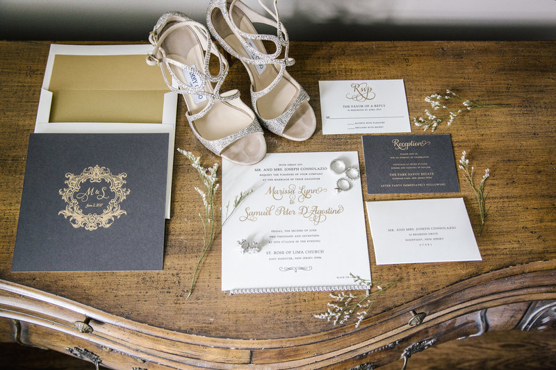 grey white and gold wedding invitations on  wood writing desk.