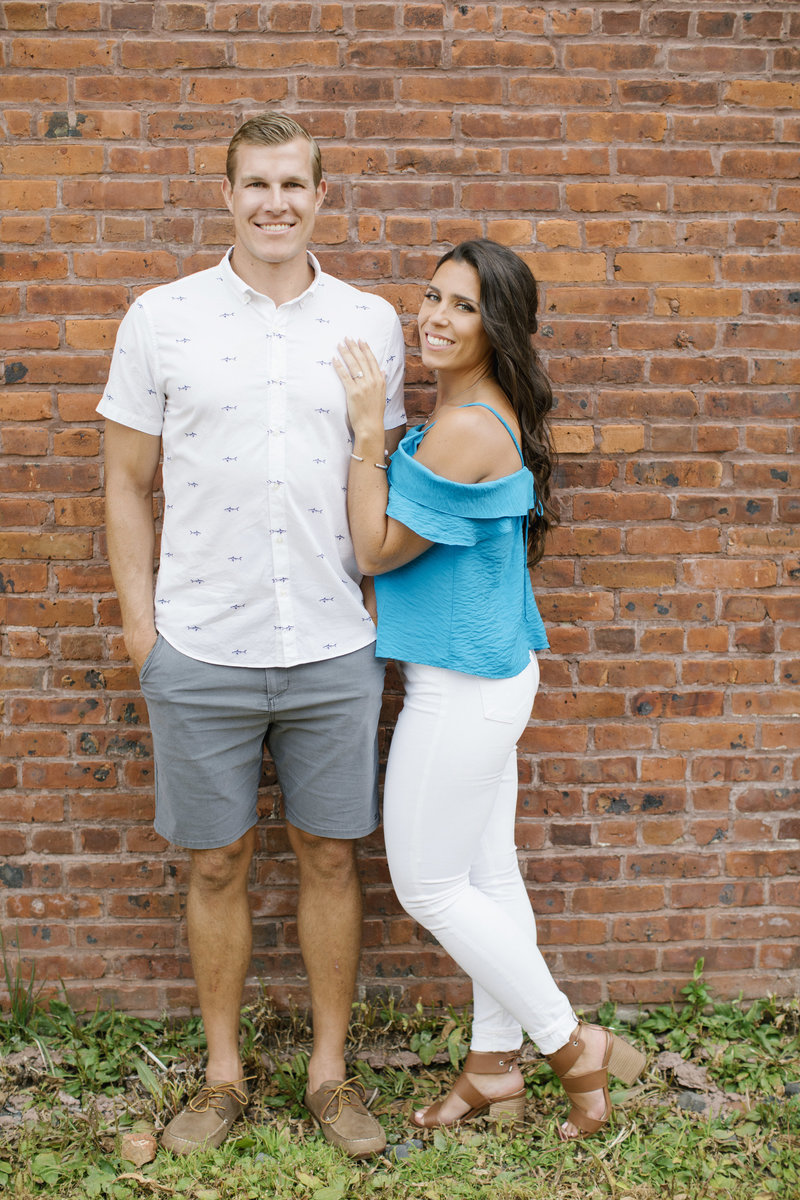 women leaning into man looking at camera in front of brick wall in summer