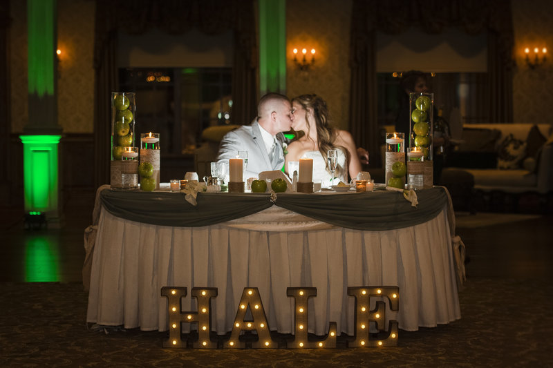 bride and groom share a kiss during the toasts