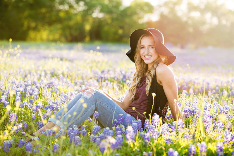 High School Senior wearing a floppy hat sitting in the bluebonnets in Grapevine, Texas