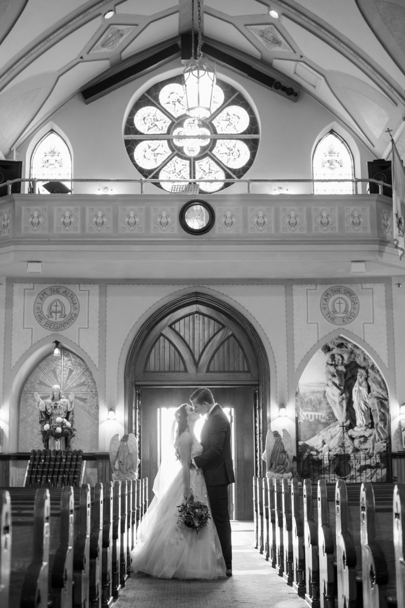 black and white bride and groom kiss in church