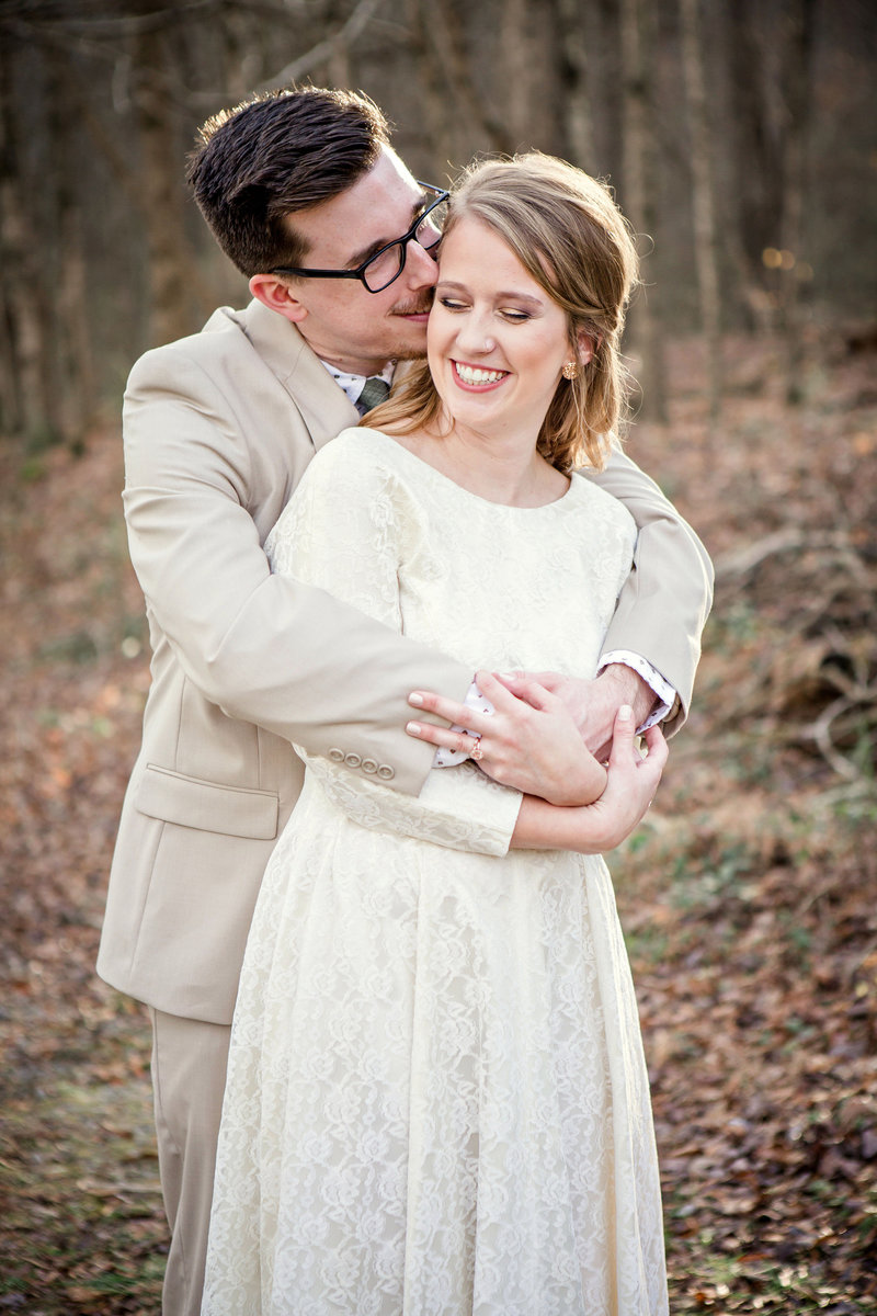 Groom hugs bride from behind in Red Clay State Park by Knoxville Wedding Photographer, Amanda May Photos.