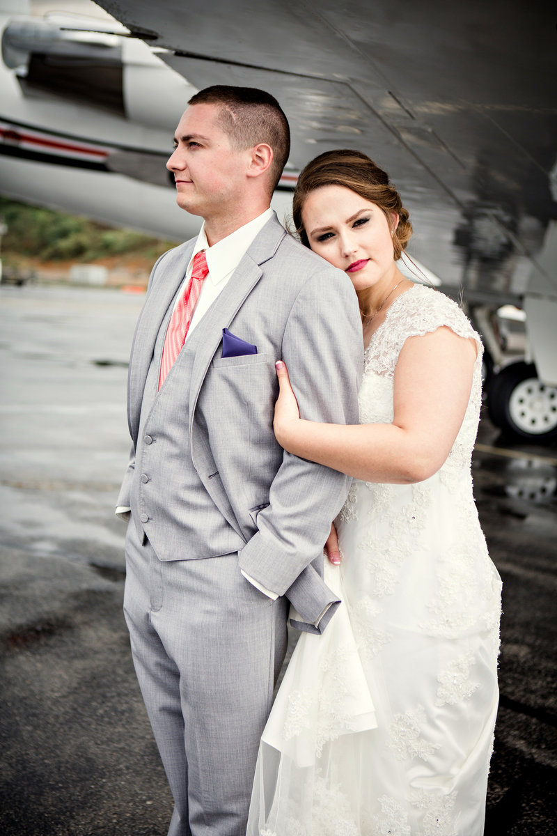 Bride resting her head on groom's shoulder underneath airplane wing by Knoxville Wedding Photographer, Amanda May Photos.