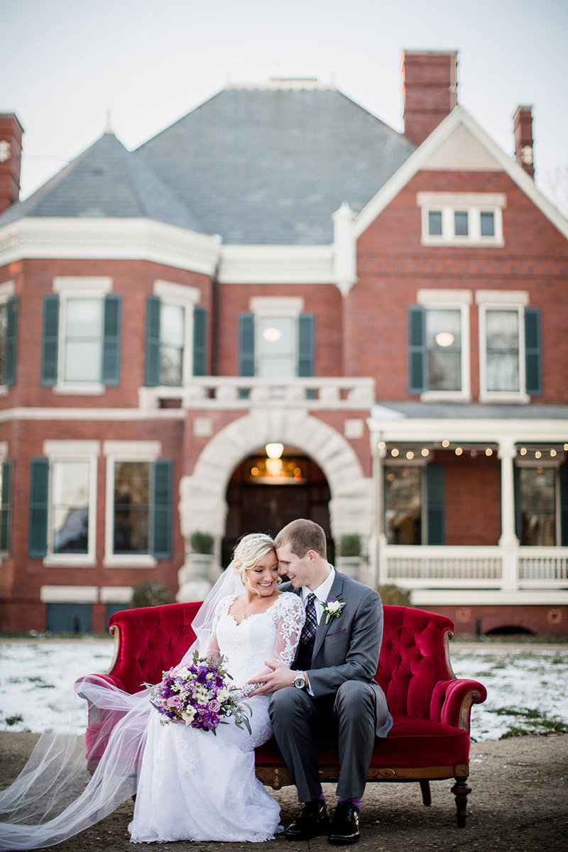 Wedding couple on red vintage couch in front of Historic Westwood Wedding Venue by Knoxville Wedding Photographer, Amanda May Photos.