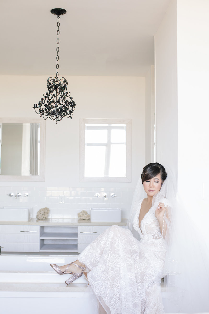 bride sitting on modern bathtub with leg kicked up