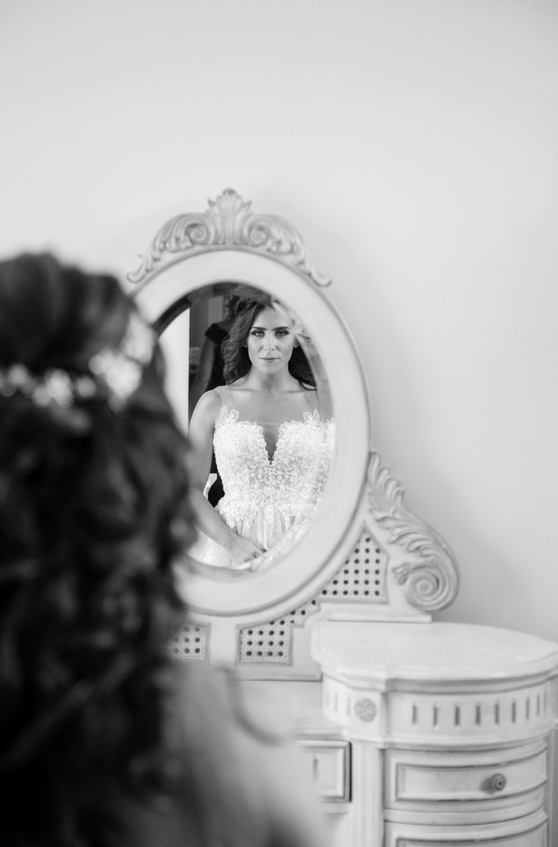 black and white photo of bride looking at reflection in vanity mirror