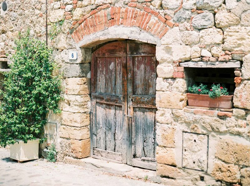 Image of old door in Monteriggioni, Tuscany. Fine art travel film photography by Rosie Reports.