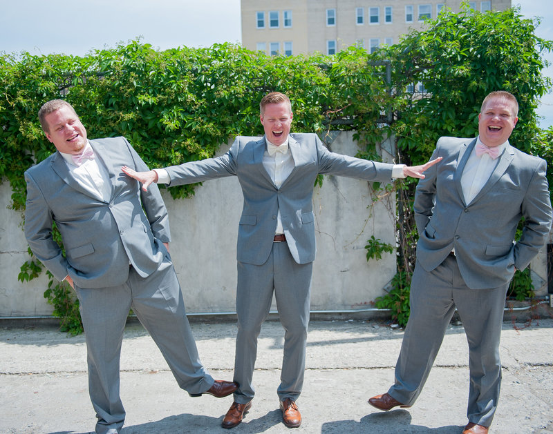 The groom has a laugh with his groomsmen in downtown Fargo pictures by Kriskandel